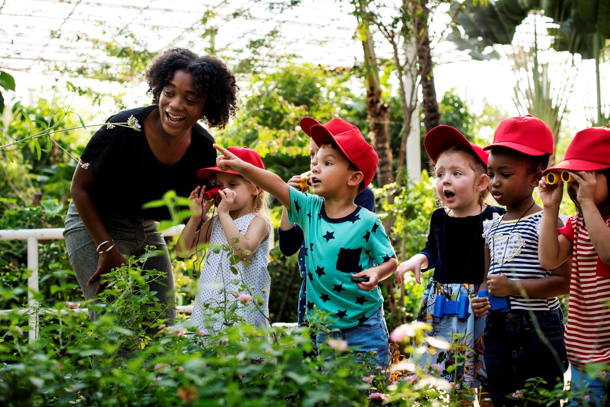 teacher and six young students wearing red hats inside a greenhouse looking at plants