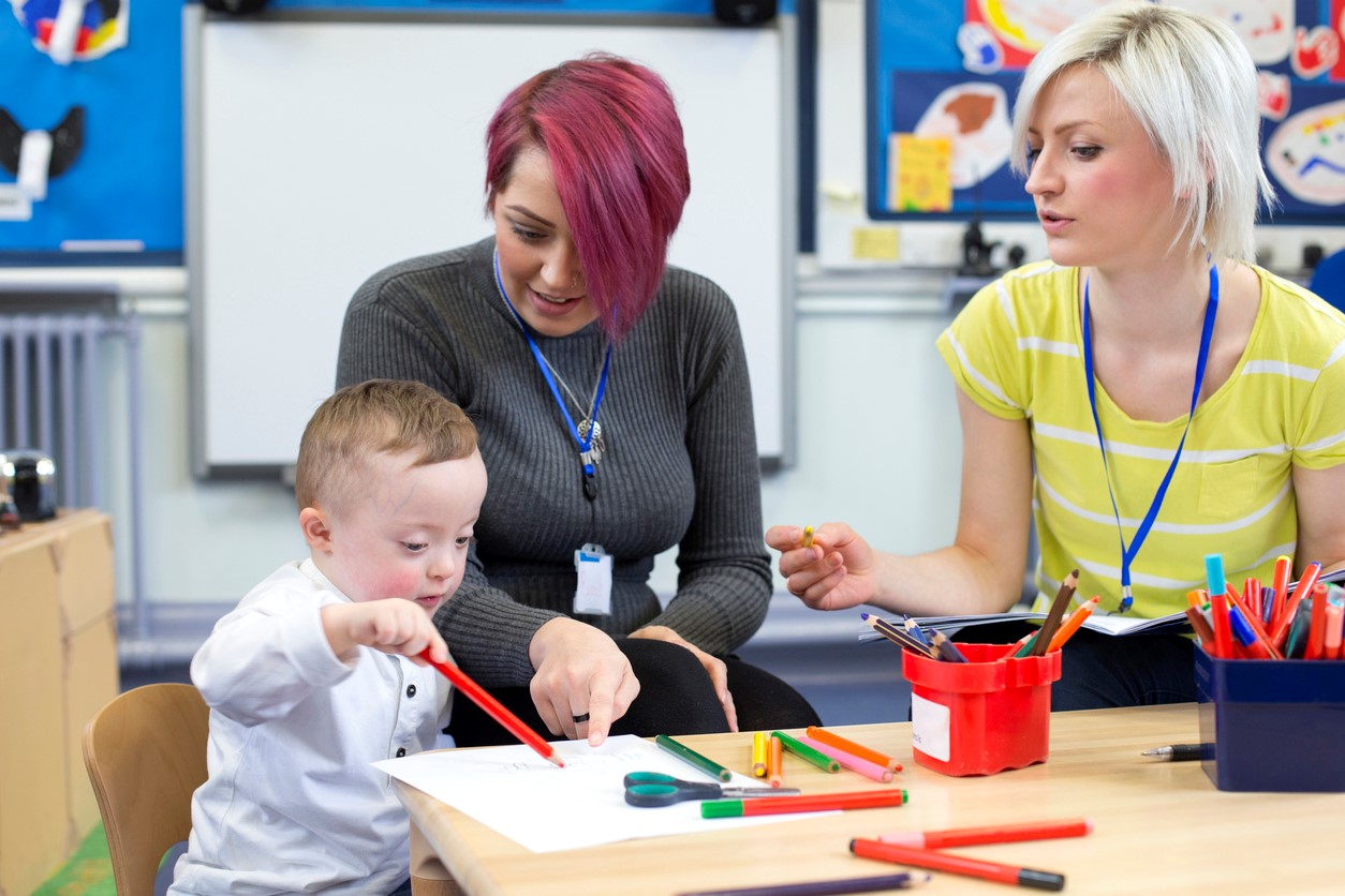 two teachers working in classroom at small round table with young boy with down syndrome
