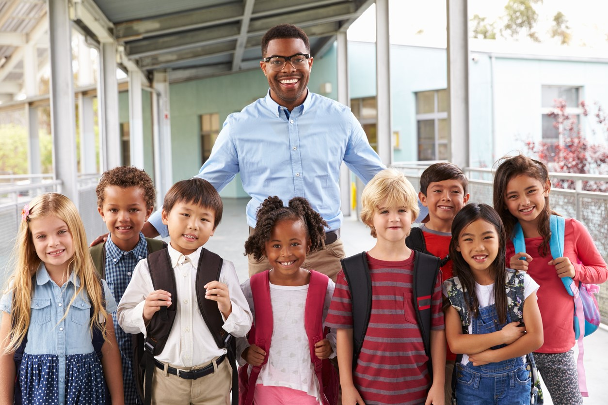 african american male teacher with eight young students from diverse backgrounds standing outside school
