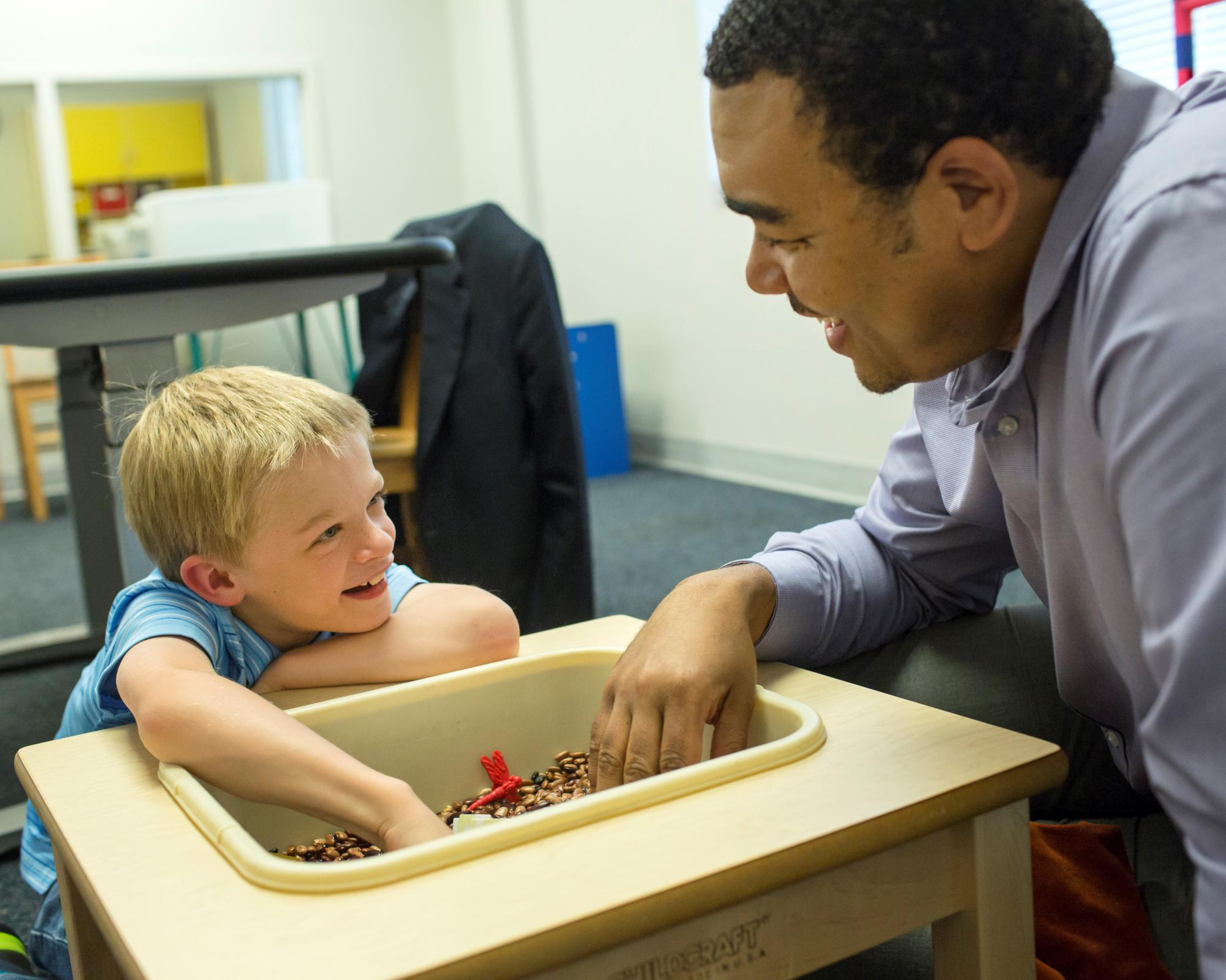 Teacher and child using sensory table