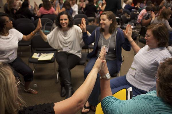 Adults sitting in a circle with hands joined together