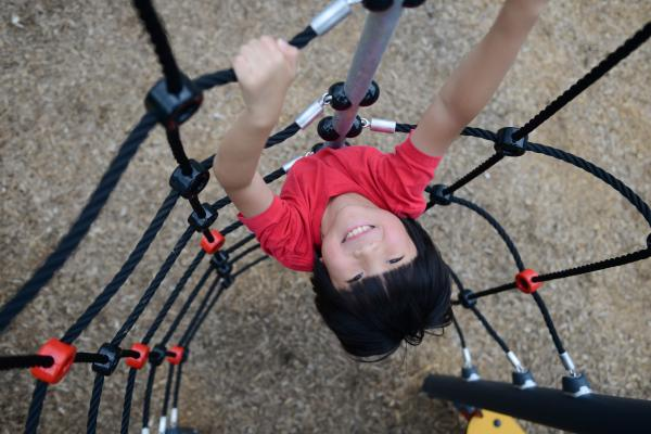 Young boy climbing a rope tower