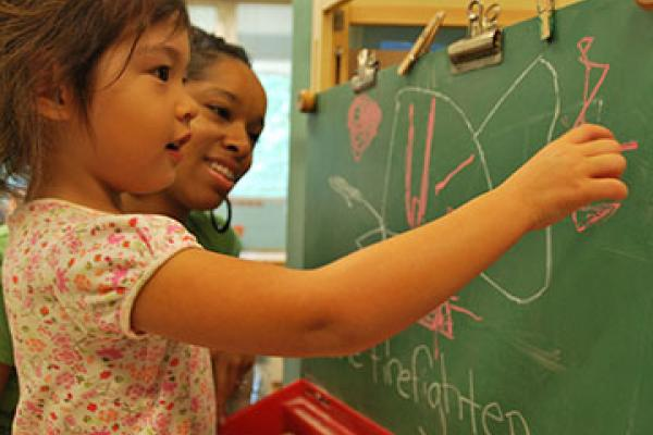 Adult with young child at a chalkboard
