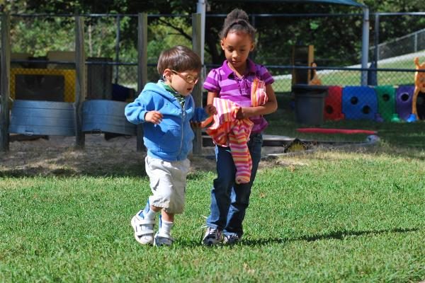 Two young children walking across playground