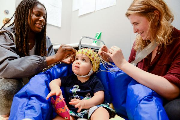 Two researchers putting sensors on a toddler