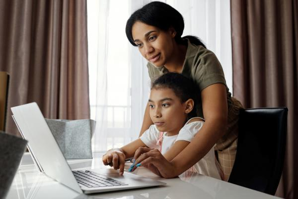 Adult helping a child to use a laptop computer