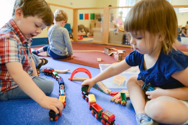 Two young children playing with trains