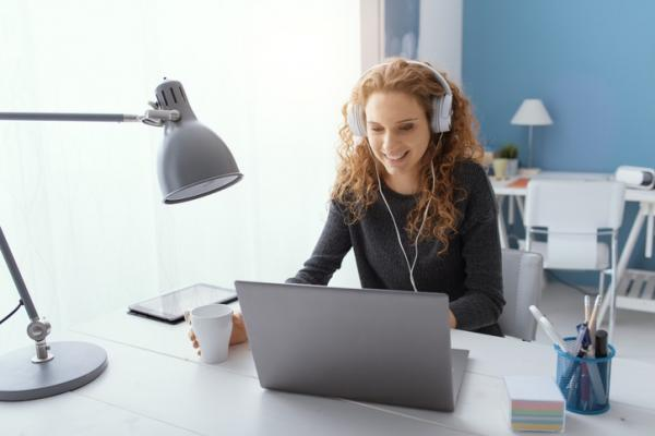 red haired woman wearing headphones working at desk