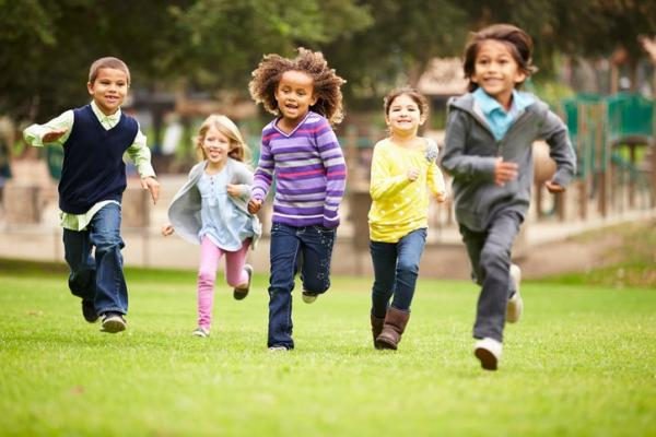 five young children running in park