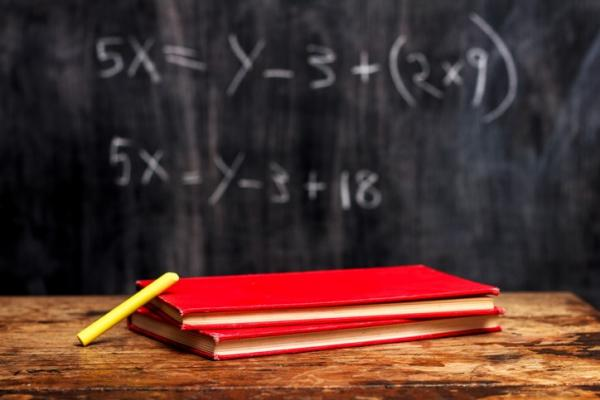 chalk board with math problems behind wooden desk with red notebooks on top