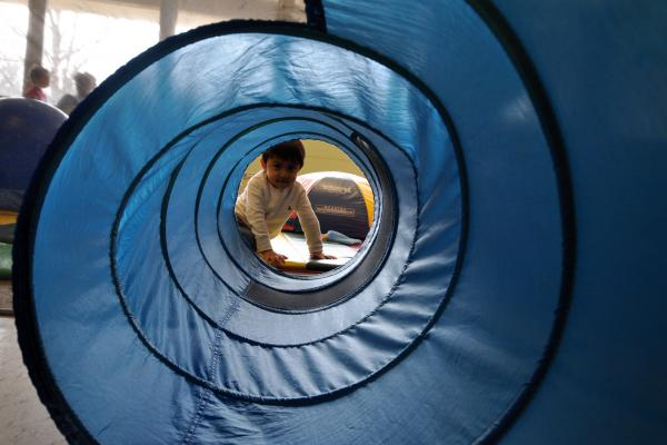 Young child peeking through play tunnel